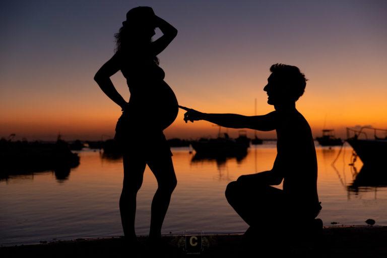 Papa montrant du doigt son futur bébé au coucher de soleil